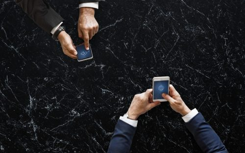Two men in suits using smartphones