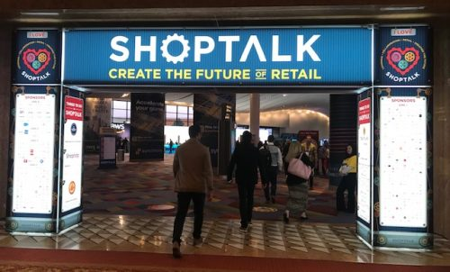 An image of attendees walking through the ShopTalk arch.